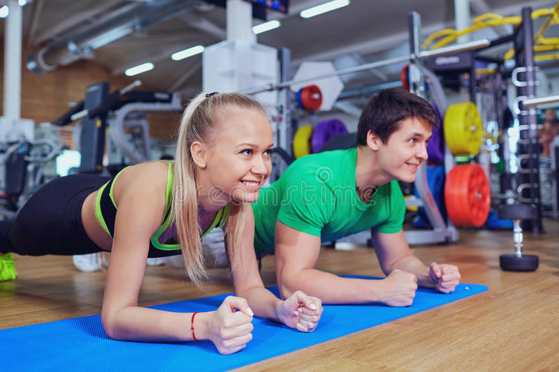 Sport couple doing pushups bar on floor in the gym stock image