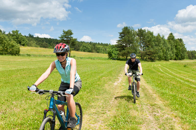 Sport couple riding mountain bicycles in stock photography