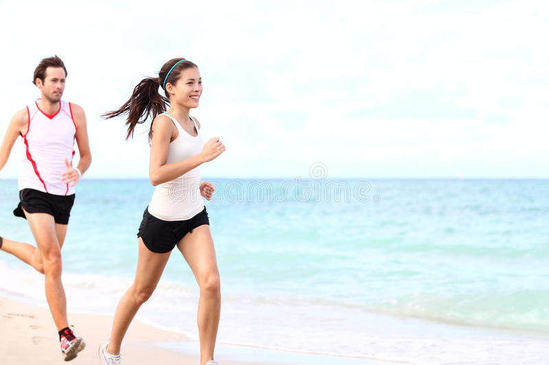 Sport - couple running. On beach traing for marathon run. Young multiracial couple runners, smiling asian female fitness model and caucasian male model