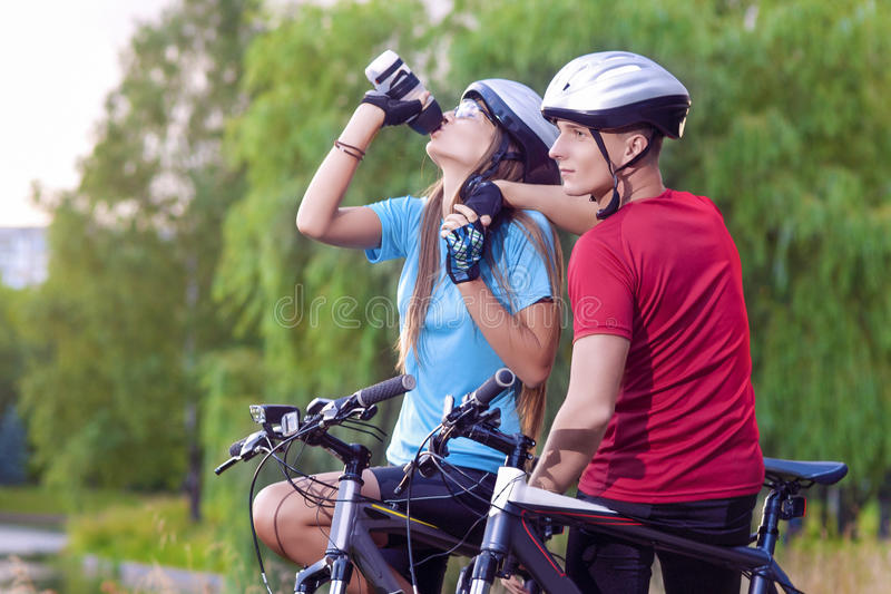 Sport and cycling Concept: Young Caucasian Cyclist Resting Toget. Her Outdoors. Having Water Break and Relaxing.Horizontal Image Composition stock photo
