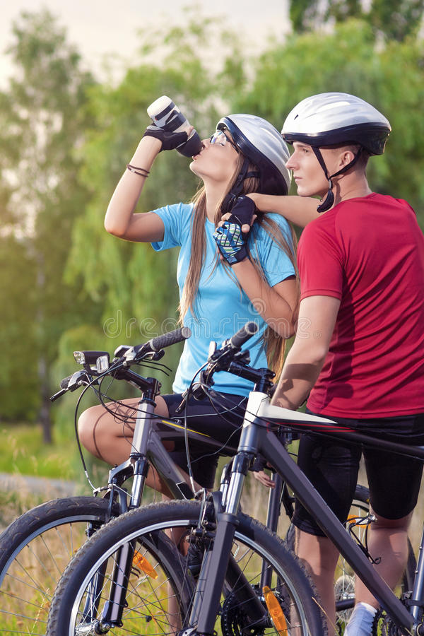 Sport and cycling Concept: Young Caucasian Cyclist Resting Toget. Her Outdoors. Having Water Break and Relaxing. Vertical Image Composition stock photography