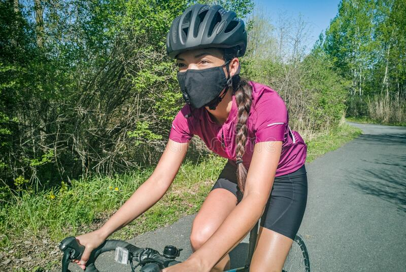 Sport cyclist woman biking on road bike wearing face mask for Covid-19 prevention during summer outdoor recreational stock image