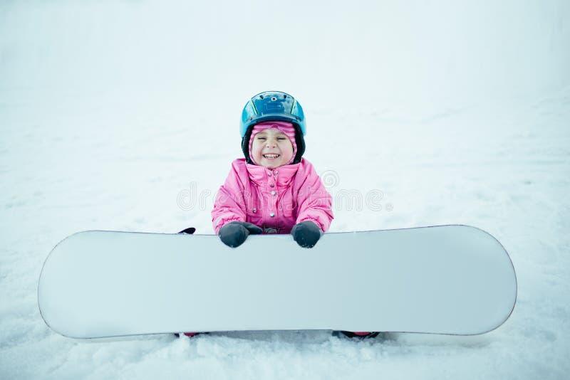 Sport d'hiver de surf des neiges Peu de fille d'enfant jouant avec la neige portant l'hiver chaud vêtx image libre de droits