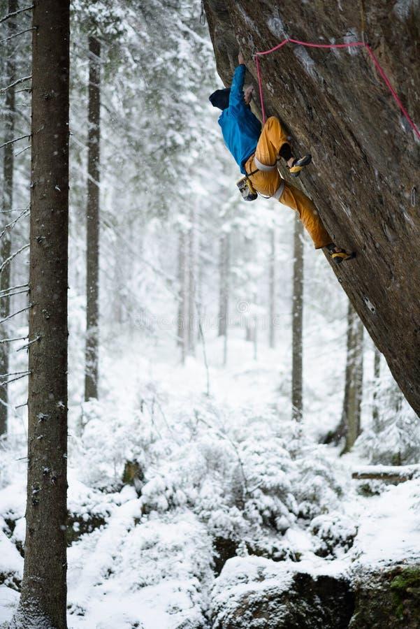 Sport d'hiver extérieur Grimpeur de roche montant une falaise provocante S'élever extrême de sport photo stock