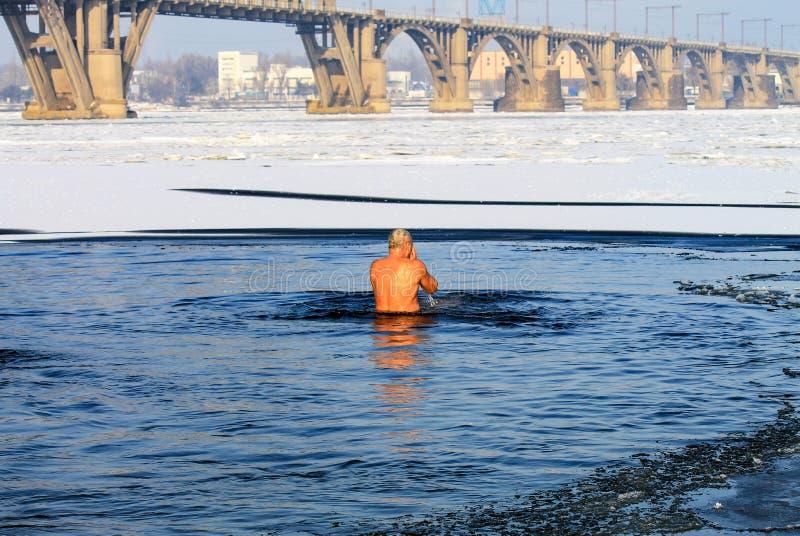 Sport d'hiver Un homme plus âgé nage en rivière d'hiver couverte de la glace pendant l'épiphanie orthodoxe de vacances durcir photos libres de droits