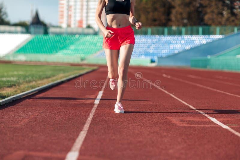 Sport De benen die van de vrouwengeschiktheid op stadion lopen Sluit omhoog van voeten van een agent De vrouwengeschiktheid stoot stock fotografie