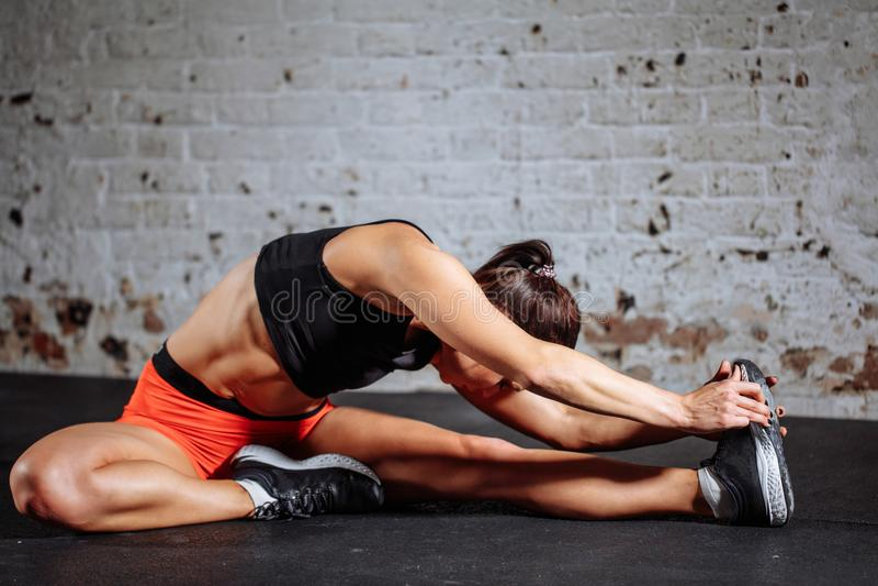 Sport de femme s'étendant dans le gymnase avec le mur de briques et les tapis noirs photographie stock