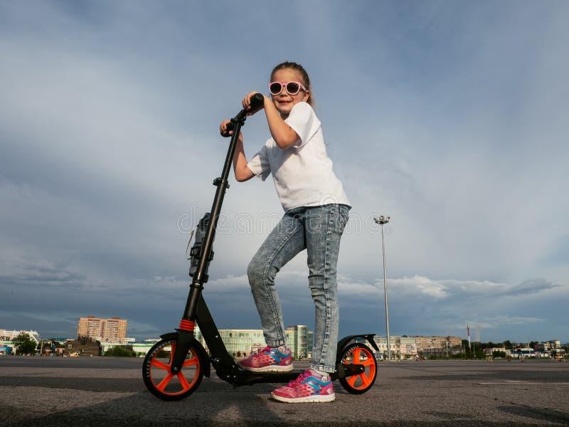 Sport de rue : Fille heureuse en montant un scooter de coup-de-pied sur le trottoir et les magmas image stock