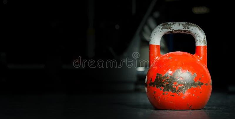 Sport della campana del bollitore, vecchio peso usato pesante del kettlebell di colore sul pavimento della palestra pronto per l' fotografia stock
