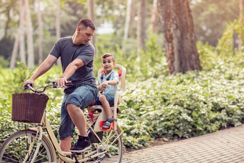 Sport della famiglia e padre in buona salute e figlio di stile di vita che guidano un bicy immagine stock