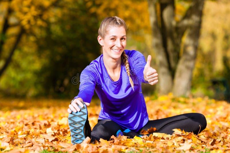 Sport della sportiva che allunga in autunno fotografie stock libere da diritti