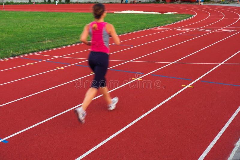 sport Den idrotts- unga kvinnan i gymnastikskor kör på rinnande spår royaltyfria foton