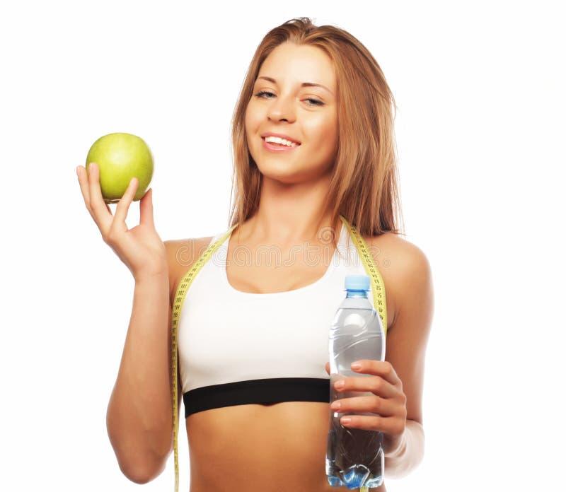 Sport, Diät, Gesundheit und Leutekonzept: Junge nette Frau in der Sportkleidung mit Apfel und einer Flasche Wasser lizenzfreies stockfoto