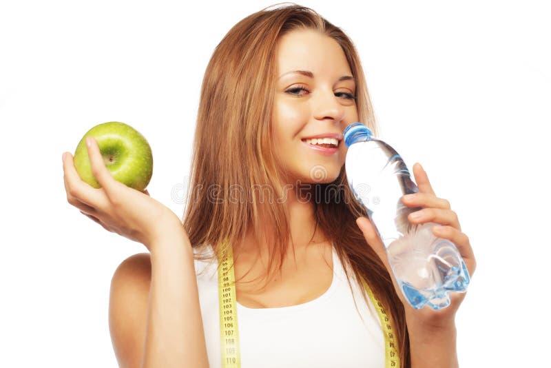 Sport, Diät, Gesundheit und Leutekonzept: Junge nette Frau in der Sportkleidung mit Apfel und einer Flasche Wasser lizenzfreie stockfotografie