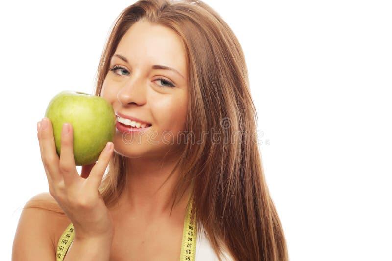 Sport, Diät, Gesundheit und Leutekonzept: Junge nette Frau in der Sportkleidung mit dem Apfel, lokalisiert über weißem Hintergrun lizenzfreie stockfotografie