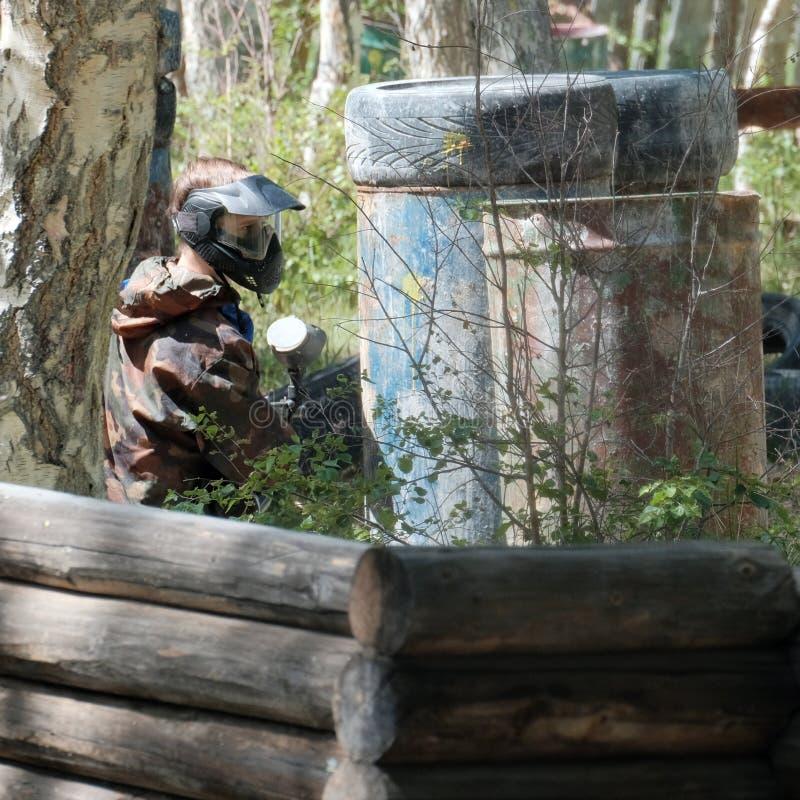 Sport di squadra estremo Il giocatore nel paintball guarda dal nascondersi Vestito del cammuffamento, maschera protettiva ed armi fotografie stock libere da diritti
