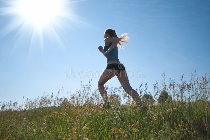 Sport die Frau, die über grünes Gras und Himmel läuft lizenzfreie stockfotografie