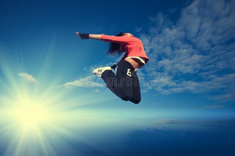 Sport die springende Frau und fliegen Sie über Himmel und Sonne lizenzfreie stockbilder