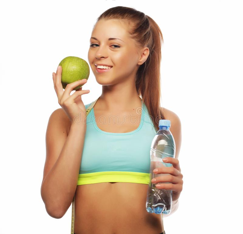 Sport, diet, health and people concept: Young cheerful woman in sports wear with apple and a bottle of water royalty free stock photo