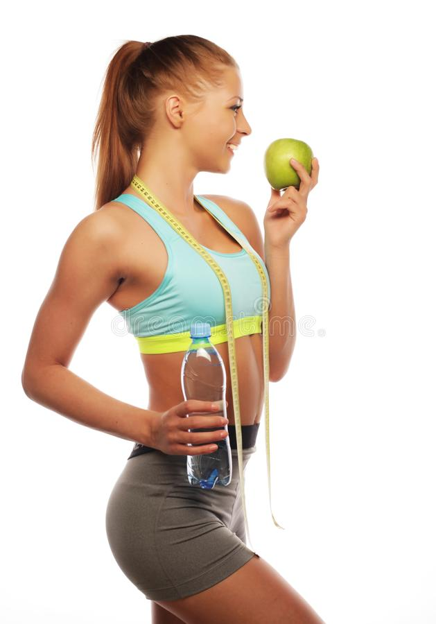 Sport, diet, health and people concept: Young cheerful woman in sports wear with apple, isolated over white background. Sport, diet, health and people concept royalty free stock images