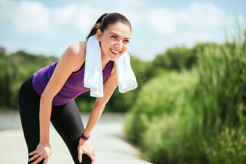 sport Donna attraente sorridente felice che rende all'aperto prima o dopo l'allenamento ed il funzionamento nel parco fotografia stock