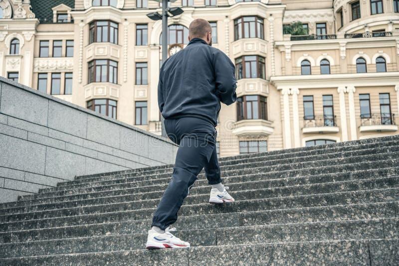 Sport duro Chiuda su dei piedi maschii che scalano le scale fuori L'uomo a forma di buono sta pareggiando all'alba immagine stock