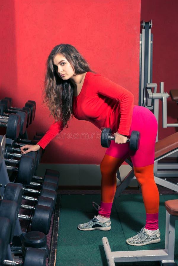 Sport dziewczyna w leggins trenuje w gym kobieta podnosi dumbbell sporta weightlifting i sprawność fizyczna obraz stock