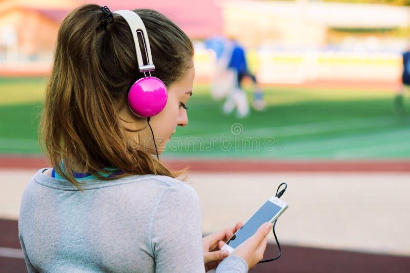Sport dziewczyna w różowych hełmofon wybiórkach muzycznych obraz royalty free