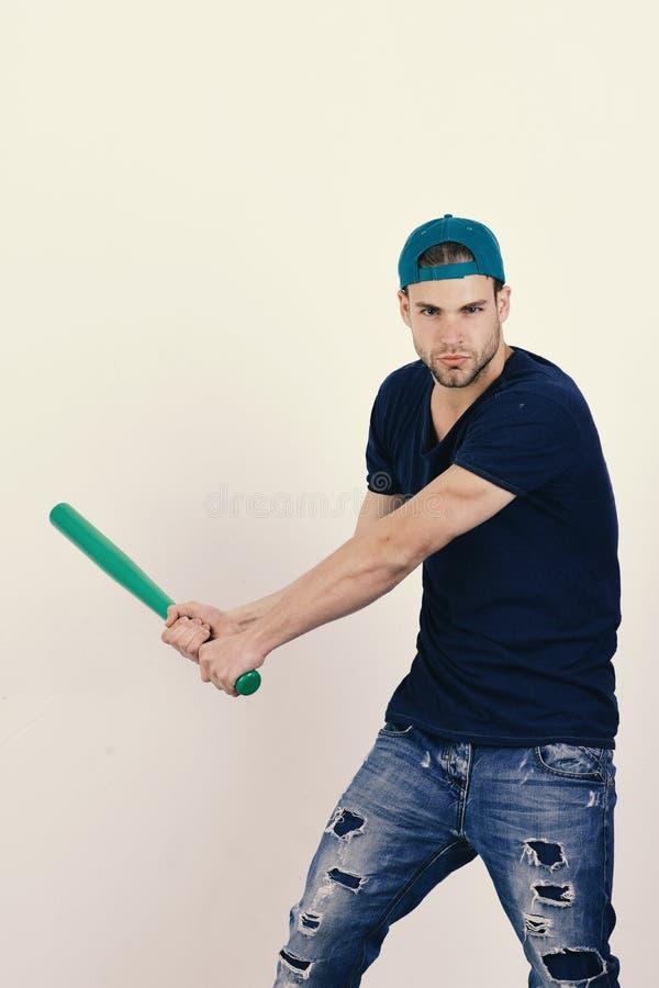 Sport e concetto di addestramento di baseball Il tipo in maglietta blu scuro tiene il pipistrello verde intenso fotografie stock