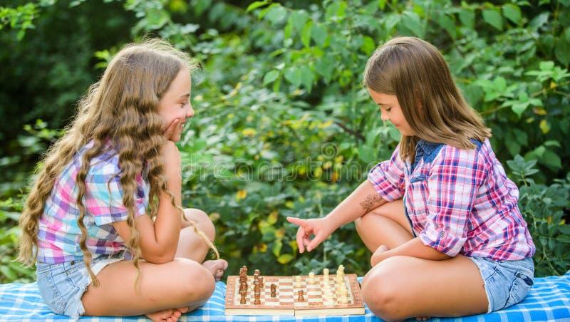 Sport e concetto di hobby Le bambine giocano a scacchi Sorelle che giocano a scacchi Sviluppo cognitivo Gioco intellettuale Marca fotografia stock
