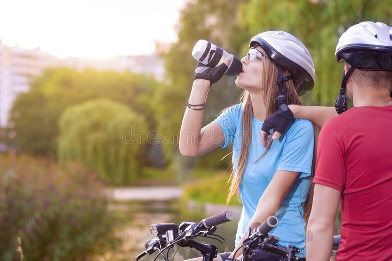 Sport e concetto di riciclaggio: Giovane ciclista caucasico che riposa Toget fotografia stock