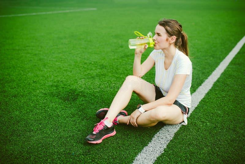 Sport e salute di tema Bella seduta della ragazza che riposa sull'erba verde, stadio artificiale del tappeto erboso che riposa la immagini stock libere da diritti