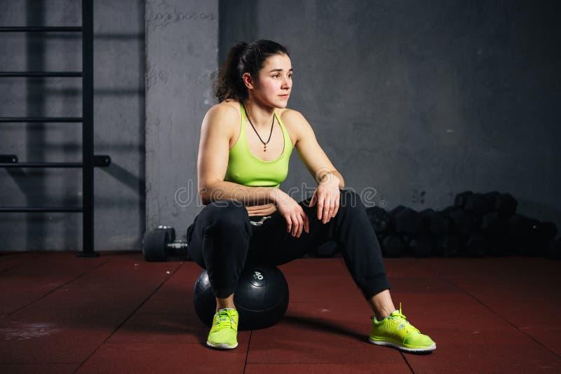 Sport e salute di tema Forte donna caucasica muscolare nella palestra che si siede su un fitball riempito pesante nero che prende fotografia stock