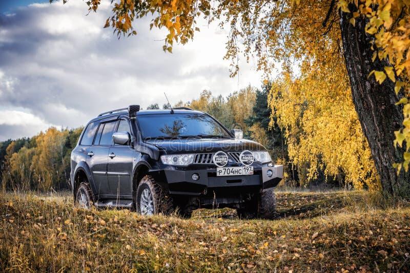 Sport ed alberi di Mitsubishi Pajero in autunno un giorno soleggiato fotografia stock libera da diritti