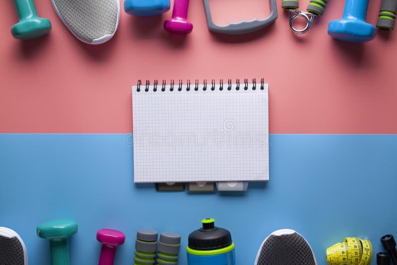Sport ed attrezzature di forma fisica e taccuino di carta classico con una pagina in bianco su fondo colorato immagine stock