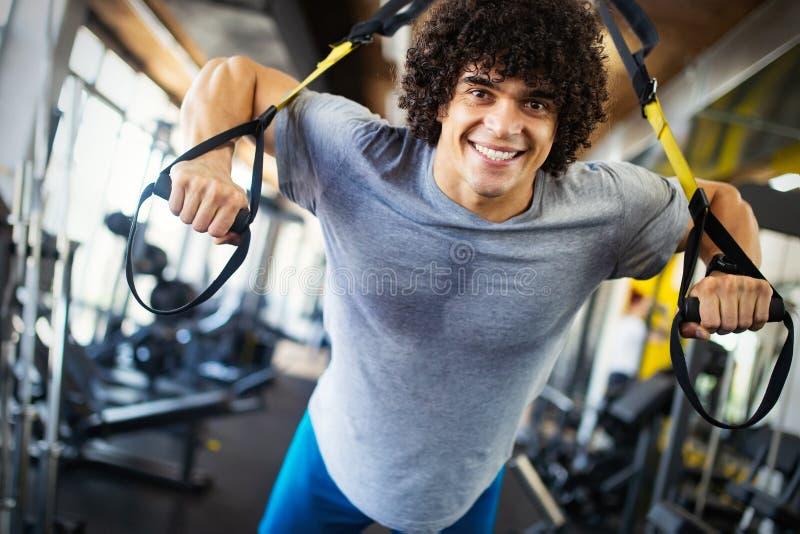 Sport, Eignung, Bodybuilding, Lebensstil und Leutekonzept - Mann, der in der Turnhalle trainiert lizenzfreies stockfoto