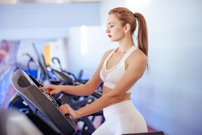 Sport, Eignung, Lebensstil, Technologie und Leutekonzept - junge Frau, die auf Tretmühle läuft stockfotos