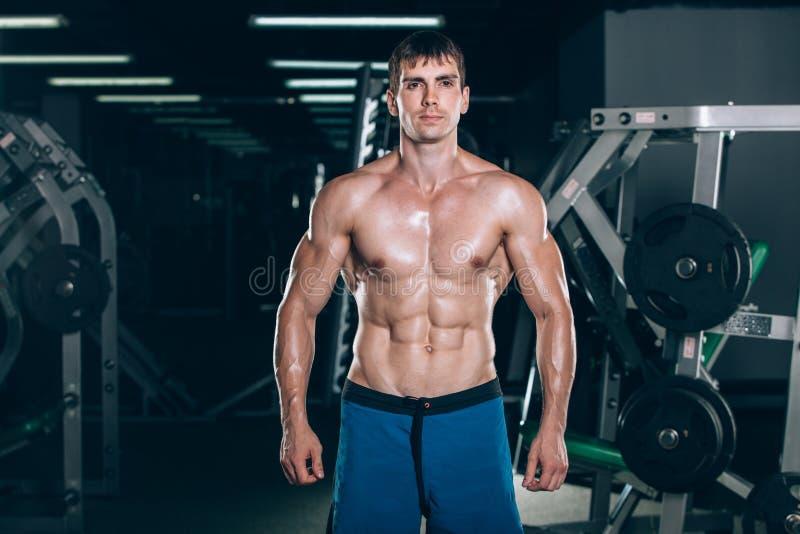 Sport, Eignung, Lebensstil und Leutekonzept - der junge stehende stark in der Turnhalle und biegende Mann mischt mit - muskulös lizenzfreie stockfotografie