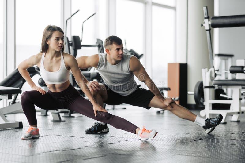 Sport, Eignung, Lebensstil und Leutekonzept - lächelnder Mann und Frau, die in Turnhalle ausdehnen lizenzfreie stockfotos