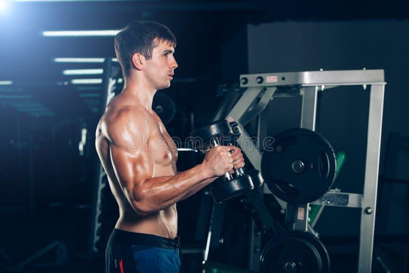 Sport, Eignung, Lebensstil und Leutekonzept - muskulöser Bodybuilderkerl, der Übungen mit Dummköpfen in der Turnhalle tut stockbild