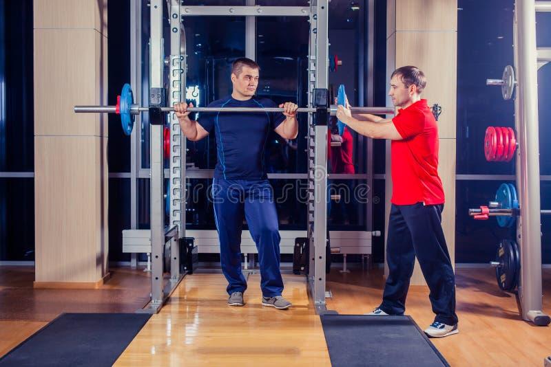 Sport, Eignung, Teamwork, bodybuildendes Leutekonzept - Mann und persönlicher Trainer mit dem Barbell, der Muskeln in der Turnhal lizenzfreie stockfotos