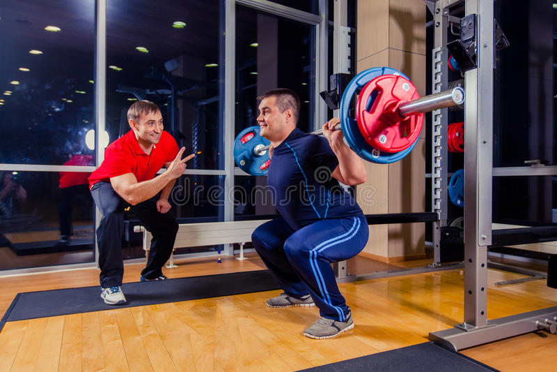 Sport, Eignung, Teamwork, bodybuildendes Leutekonzept - Mann und persönlicher Trainer mit dem Barbell, der Muskeln in der Turnhal lizenzfreie stockfotografie