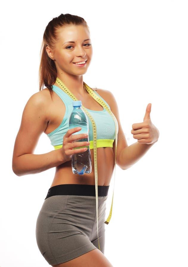 Sport, Eignung und Leutekonzept: Junge glückliche lächelnde Frau in der Sportkleidung mit Wasser, stockbild