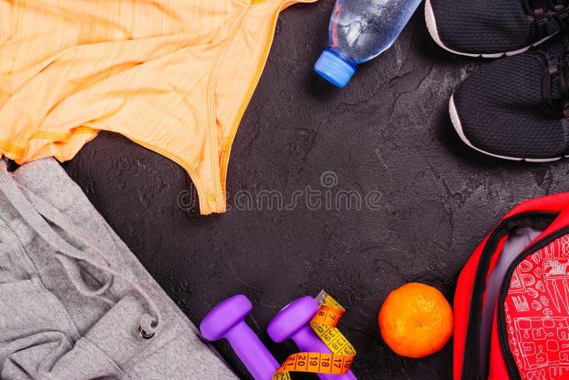 Sport- eller konditionuppsättning med kvinnliga kläder, hantlar, påsen och sportskor på svart bakgrund arkivfoto