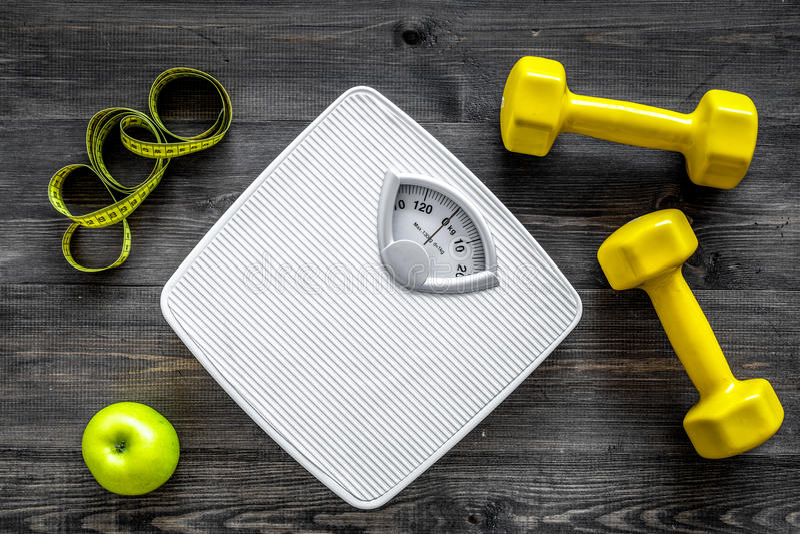 Sport en dieet voor het verliezen van gewicht Badkamersschaal, appel en domoor op houten hoogste mening als achtergrond stock foto's