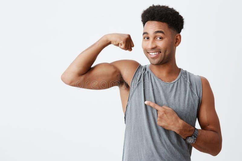 Sport en levensstijlconcept Donkere gevilde knappe mens met krullend haar die spieren tonen Het professionele sportmannen stellen stock foto