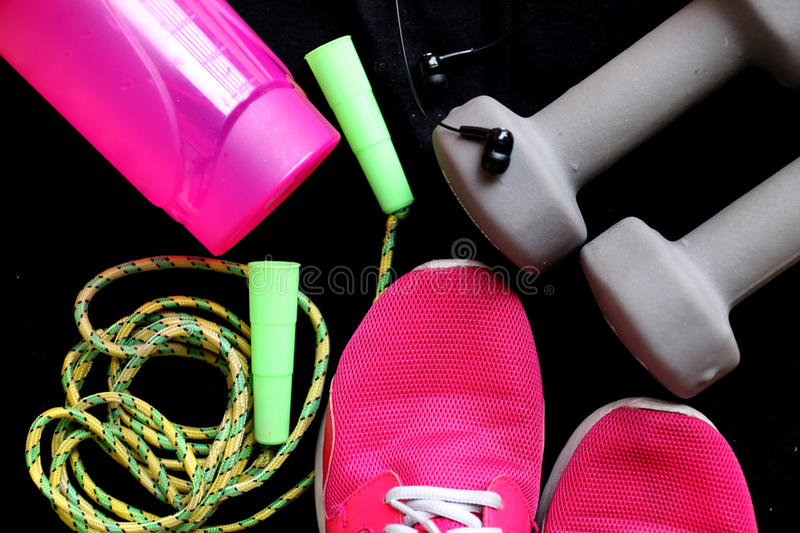 Sport equipment on black background. Sport wear, sport fashion, sport accessories. Sneakers, athletic shoes, dumbbells, headphones stock image
