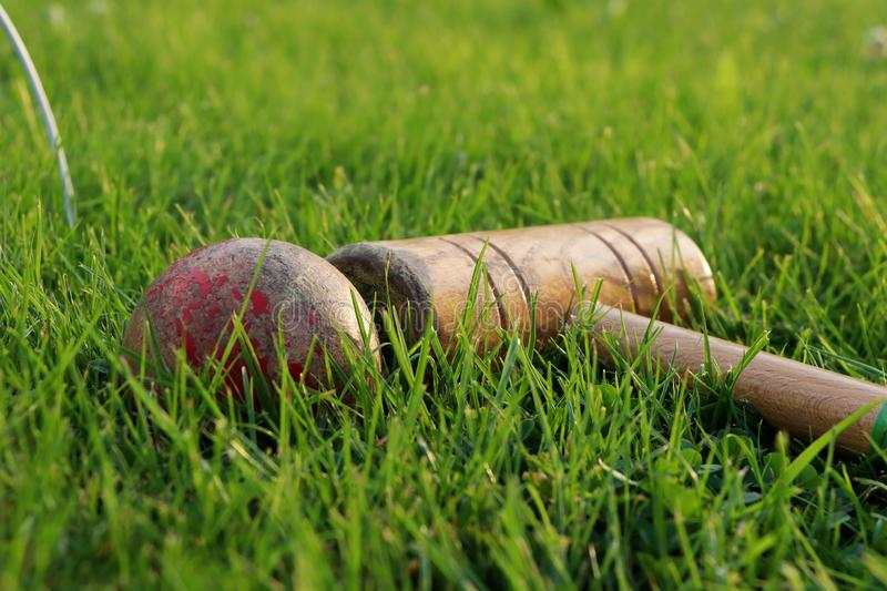 Sport equipments in green grass. Red ball, goal, cricket stick. Main sport in England stock images