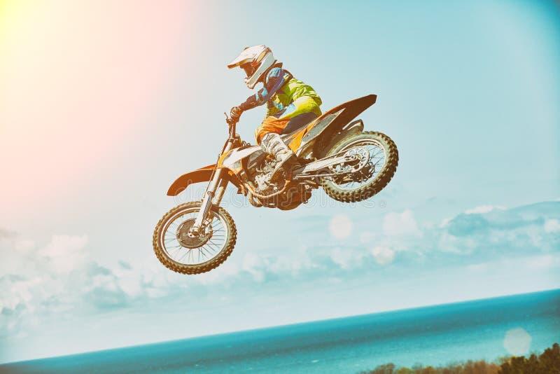 Sport estremi, salto del motociclo Il motociclista fa un salto estremo contro il cielo Sport estremi, motociclo immagine stock libera da diritti