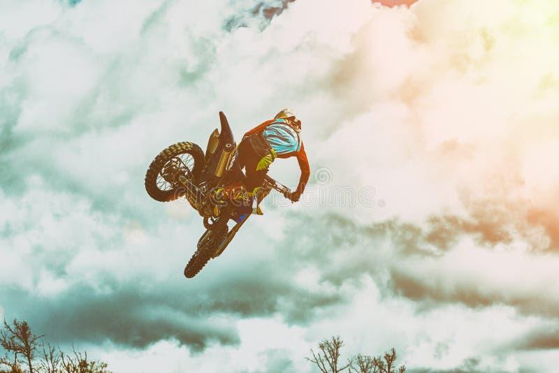Sport estremi, salto del motociclo Il motociclista fa un salto estremo contro il cielo Sport estremi, motociclo fotografia stock libera da diritti